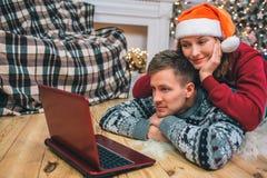 Figlarnie para na podłodze Młodej kobiety lying on the beach na mężczyzny plecy Oglądają na laptopu ekranie Ono uśmiecha się Zaba obraz royalty free
