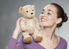 Figlarnie 20s dziewczyna trzyma jej ulubionego comforter z emocją dla niewinności i dziecka szczęścia Fotografia Stock