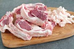 Figli i tagli ed il grasso di agnello del chopRaw su un tagliere di legno verde oliva su un fondo astratto grigio Concetto di cot immagine stock