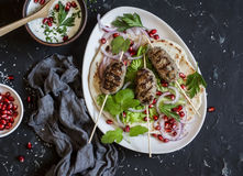 Figli il kebab su flatbread con lattuga, le cipolle ed il melograno Su una priorità bassa scura fotografia stock libera da diritti