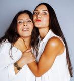 Figlia abbastanza teenager sveglia con la madre matura che abbraccia, st di modo Fotografia Stock