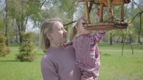 Figlia adorabile della giovane tenuta bionda della madre piccola e mostrare la sua casa dell'alimentatore dell'uccello nel parco  archivi video