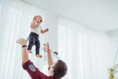 Figlia allegra di lancio dell'alta aria della mano del padre Immagini Stock