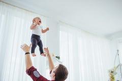 Figlia allegra di lancio dell'alta aria della mano del padre Fotografia Stock Libera da Diritti