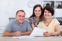 Figlia che aiuta con i documenti ai genitori fotografia stock