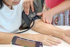 Figlia che controlla ipertensione di pressione sanguigna del ` s della madre immagine stock