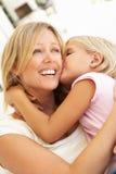 Figlia che dà bacio della madre che si distende sul sofà Immagine Stock Libera da Diritti