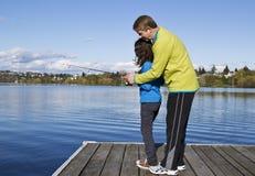 Figlia che impara pesca dal papà Immagini Stock