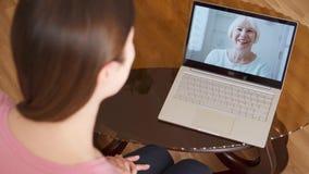 Figlia che studia all'estero avere video chiacchierata via la chiamata di app del messaggero sul computer portatile con sua madre video d archivio