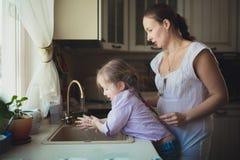 Figlia con sua madre per lavarsi le loro mani nel lavandino di cucina Immagini Stock Libere da Diritti