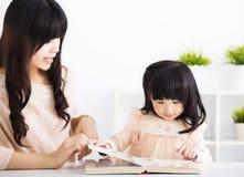Figlia d'aiuto del bambino della madre alla lettura Fotografie Stock