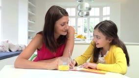 Figlia d'aiuto della madre con compito stock footage