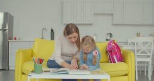 Figlia d'aiuto della madre con compito a casa stock footage