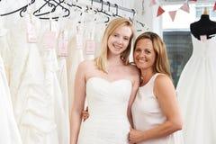 Figlia d'aiuto della madre per scegliere vestito in deposito nuziale Immagine Stock Libera da Diritti
