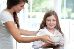 Figlia d'alimentazione della mamma cereale da prima colazione Immagine Stock