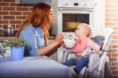 Figlia d'alimentazione della mamma che si siede su un seggiolone con il cucchiaio Invia l'un l'altro i baci Fotografie Stock Libere da Diritti