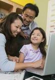 Figlia d'istruzione del padre e della madre per utilizzare computer portatile immagini stock libere da diritti