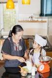 Figlia d'istruzione della madre alla farina di frumento di scavatura Fotografie Stock