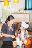 Figlia d'istruzione della madre alla farina di frumento di scavatura Immagini Stock
