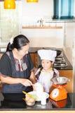 Figlia d'istruzione della madre alla farina di frumento di scavatura Fotografie Stock Libere da Diritti