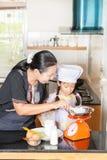 Figlia d'istruzione della madre alla farina di frumento di scavatura Fotografia Stock