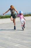 Figlia d'istruzione della madre che rollerblading Immagini Stock Libere da Diritti