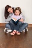 Figlia d'istruzione della madre per leggere formazione domestica Fotografia Stock Libera da Diritti