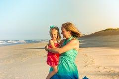 Figlia del bambino della tenuta della madre sulla spiaggia Fotografia Stock