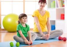 Figlia del bambino e della madre che fa gli esercizi di forma fisica sulla stuoia a casa Immagini Stock