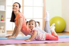 Figlia del bambino e della madre che fa gli esercizi di yoga sul pavimento nella sala a casa Famiglia divertendosi all'interno co Immagine Stock