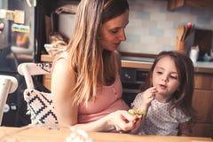 Figlia del bambino e della madre che mangia l'uva per la prima colazione a casa immagini stock
