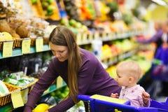 Figlia del bambino e della madre in supermercato Fotografia Stock