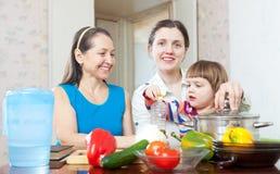 Figlia dell'adulto e della donna con il bambino in cucina Fotografia Stock Libera da Diritti