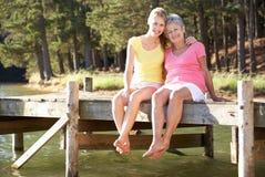 Figlia dell'adulto e della madre che si siede dal lago fotografia stock