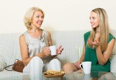 Figlia dell'adulto e della madre sul sofà Fotografia Stock