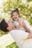 Figlia della holding del padre all'aperto Fotografie Stock