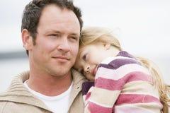 Figlia della holding del padre alla spiaggia Fotografie Stock