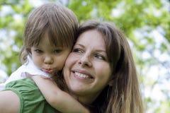 Figlia della holding della madre all'aperto che sorride Fotografia Stock Libera da Diritti