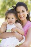Figlia della holding della madre all'aperto che sorride Fotografia Stock