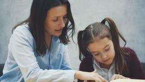 Figlia della mamma che legge un libro mentre chiacchierando Fondo grigio archivi video