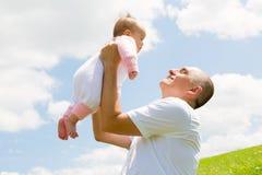 Figlia di Holds His Baby del padre alta nell'aria Immagini Stock