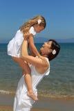 Figlia di sollevamento della madre in su sulla spiaggia Immagine Stock