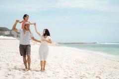 Figlia di trasporto del giovane padre sulla spalla quando goda della spiaggia con la madre fotografia stock libera da diritti