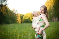 Figlia di trasporto della madre in imbracatura nel campo Fotografia Stock Libera da Diritti