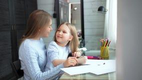 Figlia felice del bambino e della madre che gode disegnando immagine su carta facendo uso della matita variopinta archivi video
