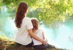 Figlia felice del bambino e della madre che si siede insieme di estate Fotografia Stock