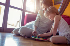 Figlia felice della ragazza e della madre che gioca sul pavimento di legno del salone Genitori rilassati felici che godono della  Immagini Stock