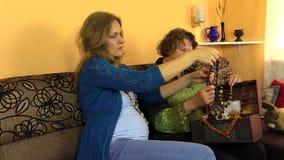 Figlia incinta con i vecchi gioielli di dimensione della madre dalla scatola del petto video d archivio