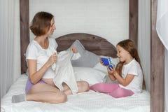 Figlia incinta del bambino e della madre che prepara abbigliamento per il neonato Immagine Stock