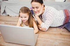 Figlia sorridente che per mezzo del computer portatile con la madre mentre trovandosi sul pavimento di legno duro fotografia stock libera da diritti